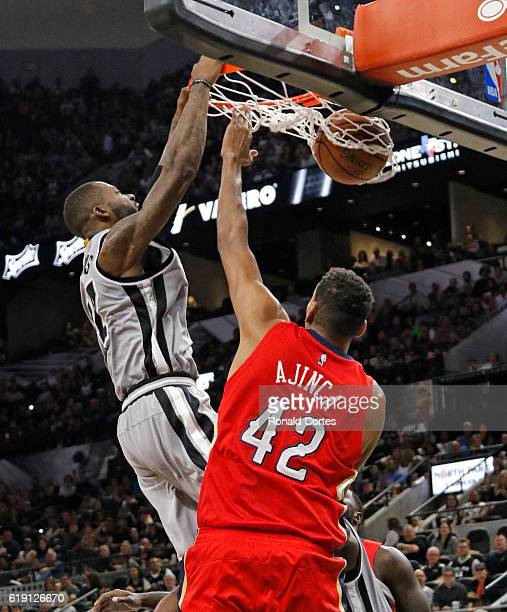 Jonathon Simmons of the San Antonio Spurs dunks over Alexis Ajinca of the New Orleans Pelicans during game between New Orleans Pelicans and the San...
