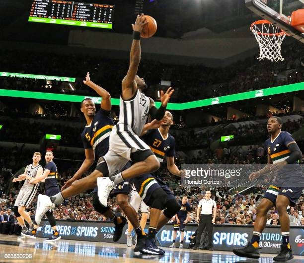 Jonathon Simmons of the San Antonio Spurs is fouled by Rodney Hood of the Utah Jazz as he drives to the basket at ATT Center on April 2 2017 in San...