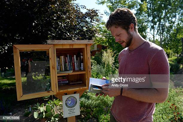 Jonathon Stalls checks out a book that was placed in his Little Free Library box at 28th and Forest July 01 2015 The boxes encourage neighbors and...