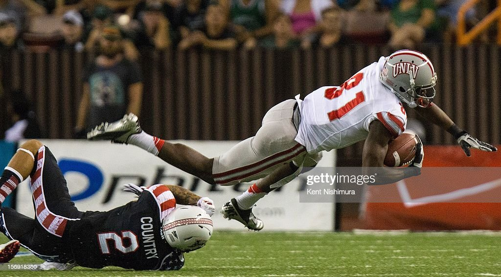 Jonavaughn Williams #31 of the UNLV Rebels is stopped by Tony Grimes #2 of the Hawaii Warriors during a NCAA college football game between the UNLV Rebels and the Hawaii Warriors on November 24, 2012 at Aloha Stadium in Honolulu, Hawaii.