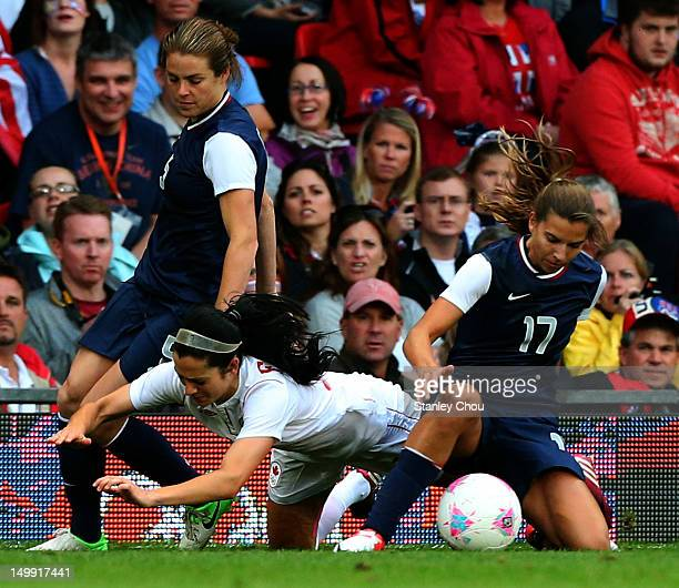 Jonelle Filigno of Canada is brought down by Tobin Heath and Kelley O'hara of USA during the Women's Football Semi Final match between Canada and USA...