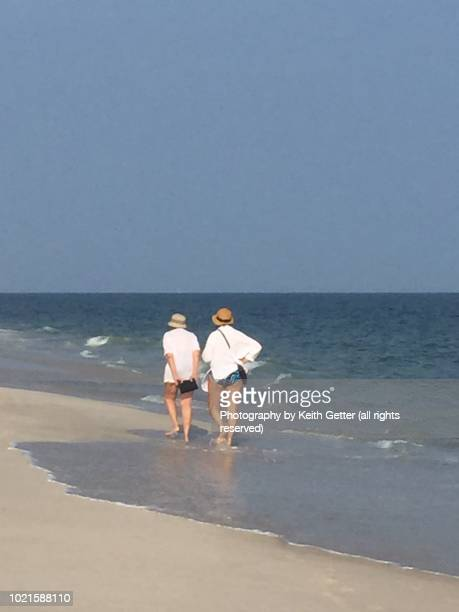 jones beach state park: two unrecognizable women walking alongside the ocean - wantagh stock pictures, royalty-free photos & images