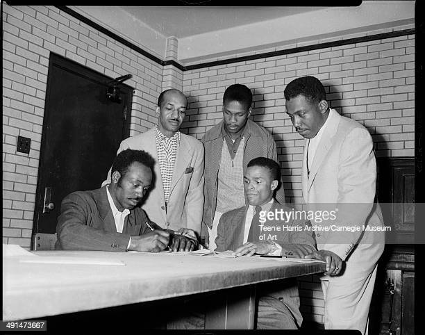 DM Jones signing to manage North Side Elks Little League baseball team with Jasper Campbell seated on right and standing from left John McCollum...