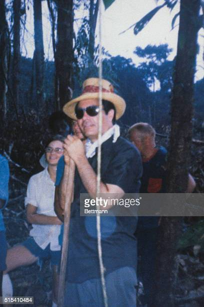 Jim Jones is shown wearing a straw hat and leaning on a stick while clearing area for his visionary Jonestown