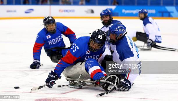 Jong Ho Jang of Korea battles for the puck with Florian Planker of Italy in the Ice Hockey bronze medal game between Korea and Italy during day eight...