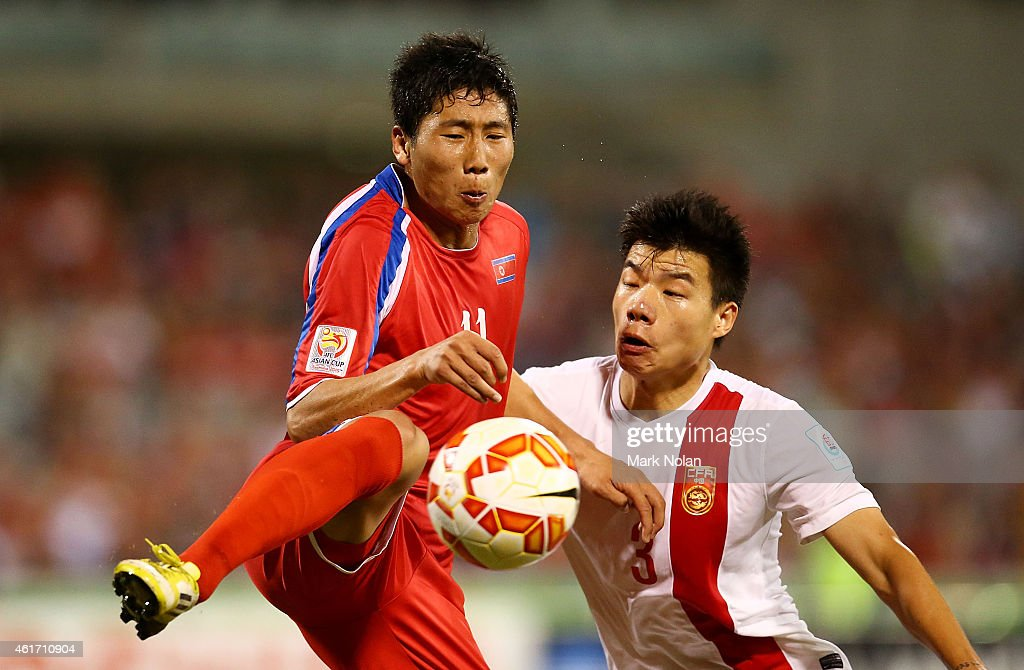 Jong Il Gwan of DPR Korea and Mei Fang of China contest possession during the 2015 Asian Cup match between China PR and DPR Korea at Canberra Stadium on January 18, 2015 in Canberra, Australia.