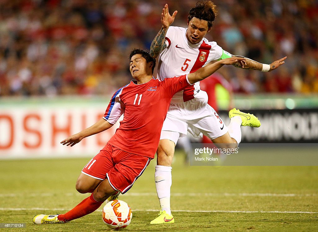 Jong Il Gwan of DPR Korea is tackled by Zhang Linpeng of China during the 2015 Asian Cup match between China PR and DPR Korea at Canberra Stadium on January 18, 2015 in Canberra, Australia.