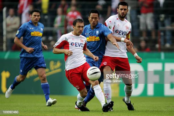Jong Taese of Bochum is challenged by Sead Mehic and Marko Kopilas of Offenbach during the DFB Cup first round match between Kickers Offenbach and...