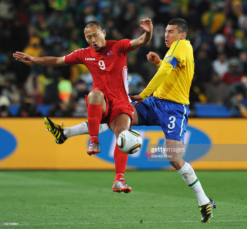 Jong Tae-Se of North Korea is tackled by Lucio of Brazil during the 2010 FIFA World Cup South Africa Group G match between Brazil and North Korea at Ellis Park Stadium on June 15, 2010 in Johannesburg, South Africa.
