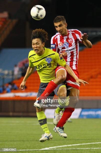 Jongwon Lee of Busan I'Park FC of Korea and Kristan Konstantinidis of the Melbourne Heart FC of Australia collide as they battle for the ball during...