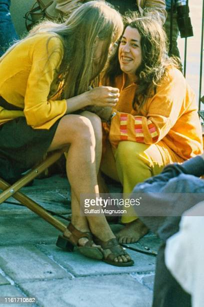 Joni Mitchell in a golden colored longsleeve blouse bending over to speak with and Cass Elliot who is squatting on the ground beside her in an orange...
