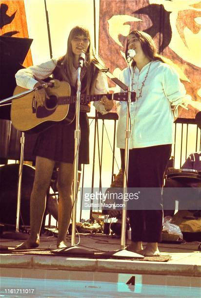 Joni Mitchell on guitar and Cass Elliot in a white top performing on the poolside stage Big Sur Hot Springs later Escalen Institute home of the human...