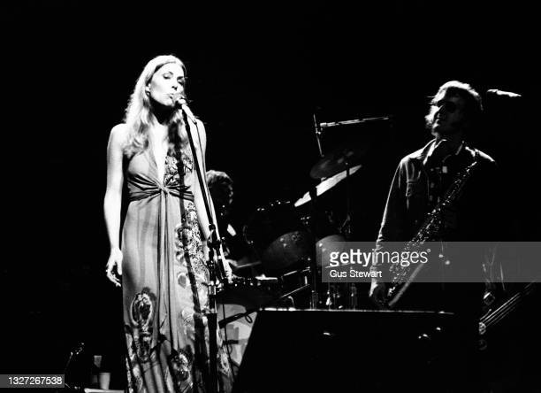Joni Mitchell performs on stage with Tom Scott of the LA Express at the New Victoria Theatre, London, England, on April 21st, 1974.