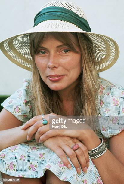 Joni Mitchell rests outside wearing a sunhat Mitchell remains one of the most acclaimed songwriters and performers of rock music since the sixties