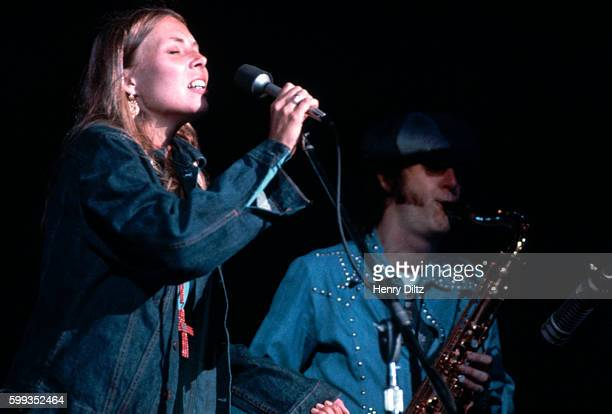 Joni Mitchell stands at a microphone to sing at a concert at the Troubadour