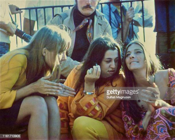 Joni Mitchell with hands clapping leaning in towards Cass Elliot with a cigarette as they both join Judy Collins who is singing and clapping Big Sur...