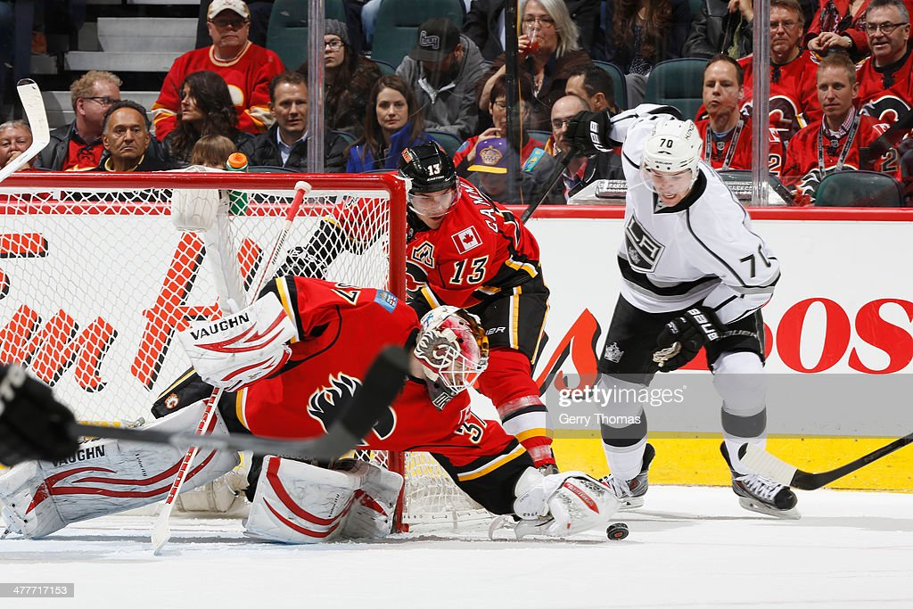 Joni Ortio #37 and Michael Cammalleri #13 of the Calgary Flames defend the net in a game against Tanner Pearson #70 of the Los Angeles Kings at Scotiabank Saddledome on March 10, 2014 in Calgary, Alberta, Canada.