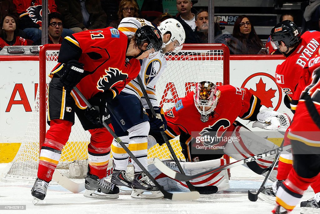 Joni Ortio #37 covers up the puck as Mikael Backlund of the Calgary Flames defends the crease against Cory Conacher #88 of the Buffalo Sabres at Scotiabank Saddledome on March 18, 2014 in Calgary, Alberta, Canada.