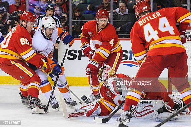Joni Ortio of the Calgary Flames stops the shot of Cal Clutterbuck of the New York Islanders during an NHL game at Scotiabank Saddledome on March 7...