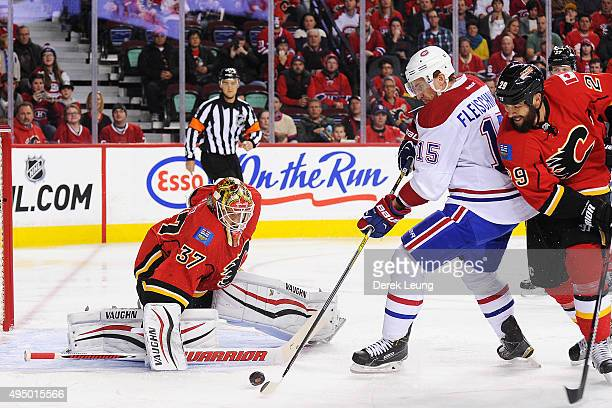 Joni Ortio of the Calgary Flames stops the shot of Tomas Fleischmann of the Montreal Canadiens during an NHL game at Scotiabank Saddledome on October...