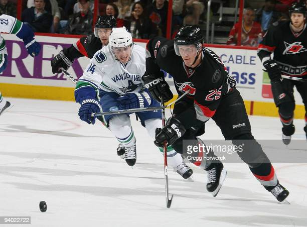 Joni Pitkanen of the Carolina Hurricanes carries the puck away from Alexandre Burrows of the Vancouver Canucks during a NHL game on December 5 2009...