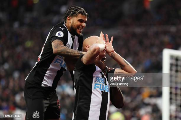Jonjo Shelvey of Newcastle United celebrates with teammate Deandre Yedlin after scoring his team's third goal during the Premier League match between...