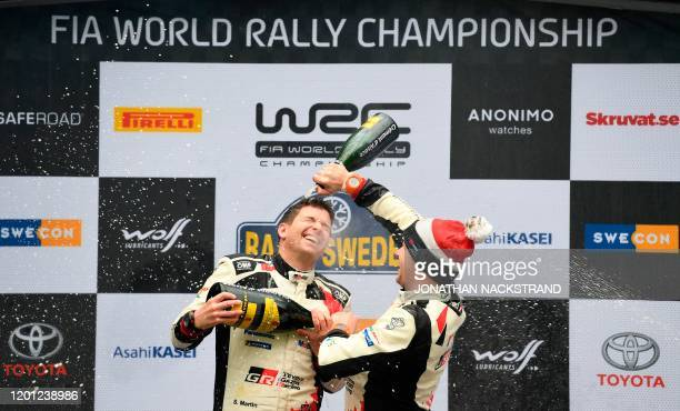 Jonne Halttunen codriver of the third placed team from Finland pours sparkling wine on the head of Scott Martin codriver of the winning team from...