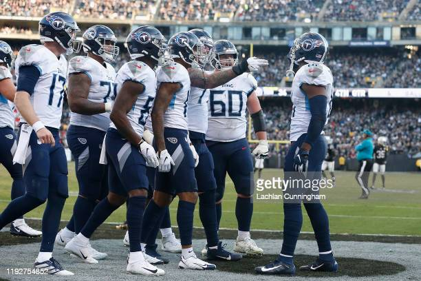 Jonnu Smith of the Tennessee Titans celebrates with teammates after scoring a touchdown in the fourth quarter against the Oakland Raiders at...