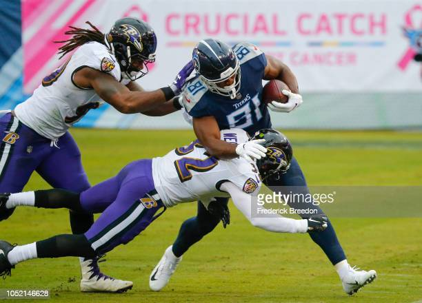 Jonnu Smith of the Tennessee Titans runs with the ball while defended by Eric Weddle of the Baltimore Ravens during the second quarter at Nissan...