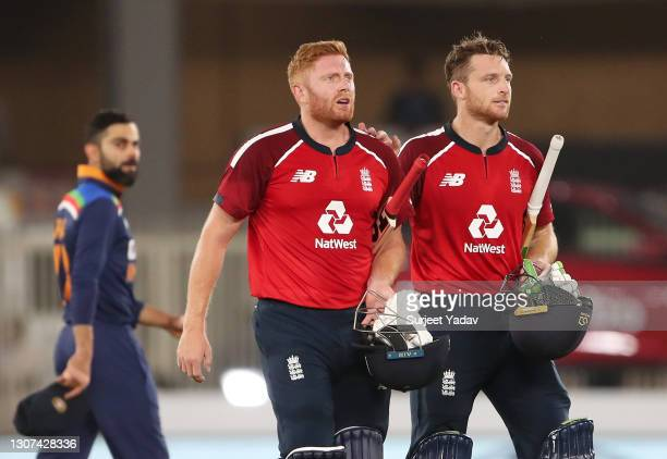 Jonny Bairstow and Jos Buttler of England walk off after victory watched on by Virat Kohli of India in the 3rd T20 International between India and...