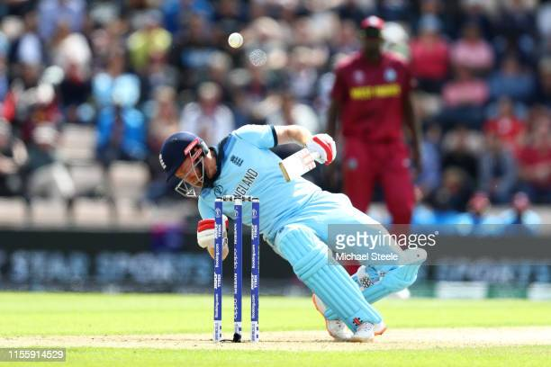 Jonny Bairstow of England falls after being hit on the helmet by a delivery from Andre Russell during the Group Stage match of the ICC Cricket World...