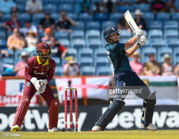 Jonny Bairstow of England hits 6 as Shai Hope of West Indies watches during the 4th ODI between West Indies and England at Grenada National Cricket...