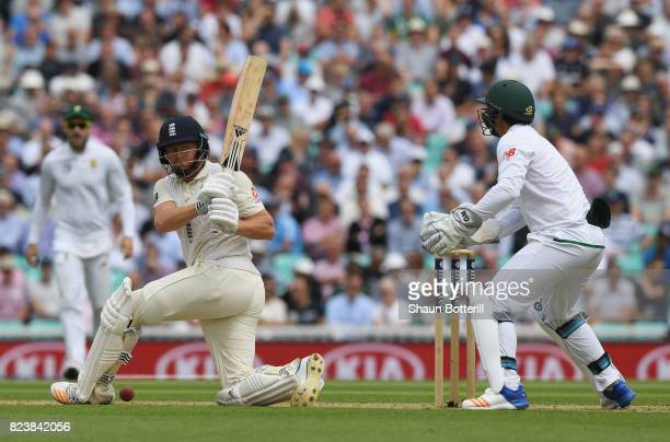 Jonny Bairstow of England plays a shot as South Africa wicket keeper Quinton de Kock looks on during day two of the 3rd Investec Test match between...