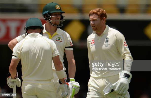 Jonny Bairstow of England walks past Cameron Bancroft and David Warner during the first Ashes cricket test match between Australia and England at the...