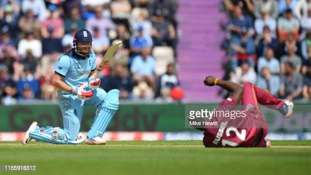 Jonny Bairstow of England watches on one knee as Andre Russell of West Indies tumbles during the Group Stage match of the ICC Cricket World Cup 2019...