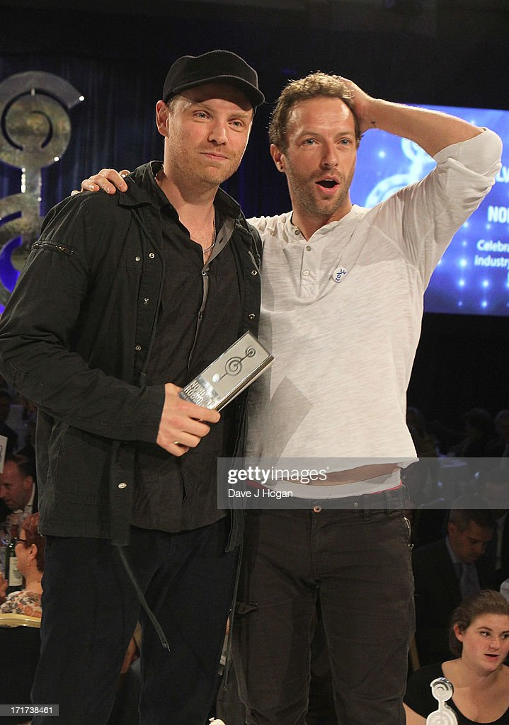 Jonny Buckland and Chris Martin of Coldplay win the Royal Albert Hall Best British Act Award at the Nordoff Robbins Silver Clef Awards at London Hilton on June 28, 2013 in London, England.