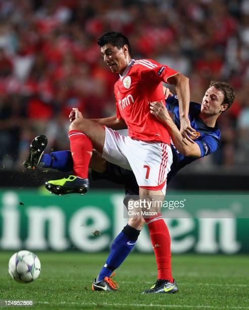Jonny Evans of Manchester United challenges Oscar Cardozo of SL Benfica during the UEFA Champions League Group C match between SL Benfica and...