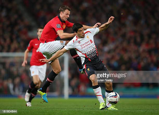 Jonny Evans of Manchester United competes with Luis Suarez of Liverpool during the Capital One Cup Third Round match betwen Manchester United and...