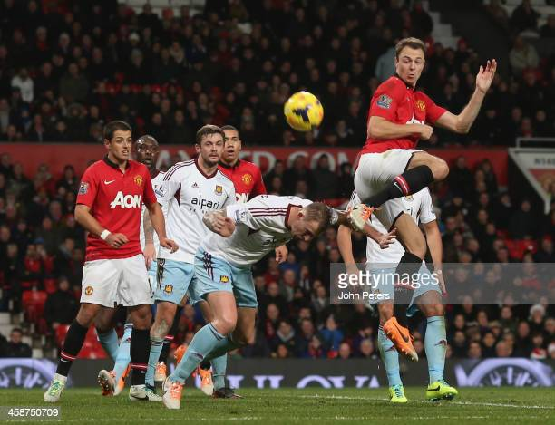 Jonny Evans of Manchester United in action with George McCartney of West Ham United during the Barclays Premier League match between Manchester...