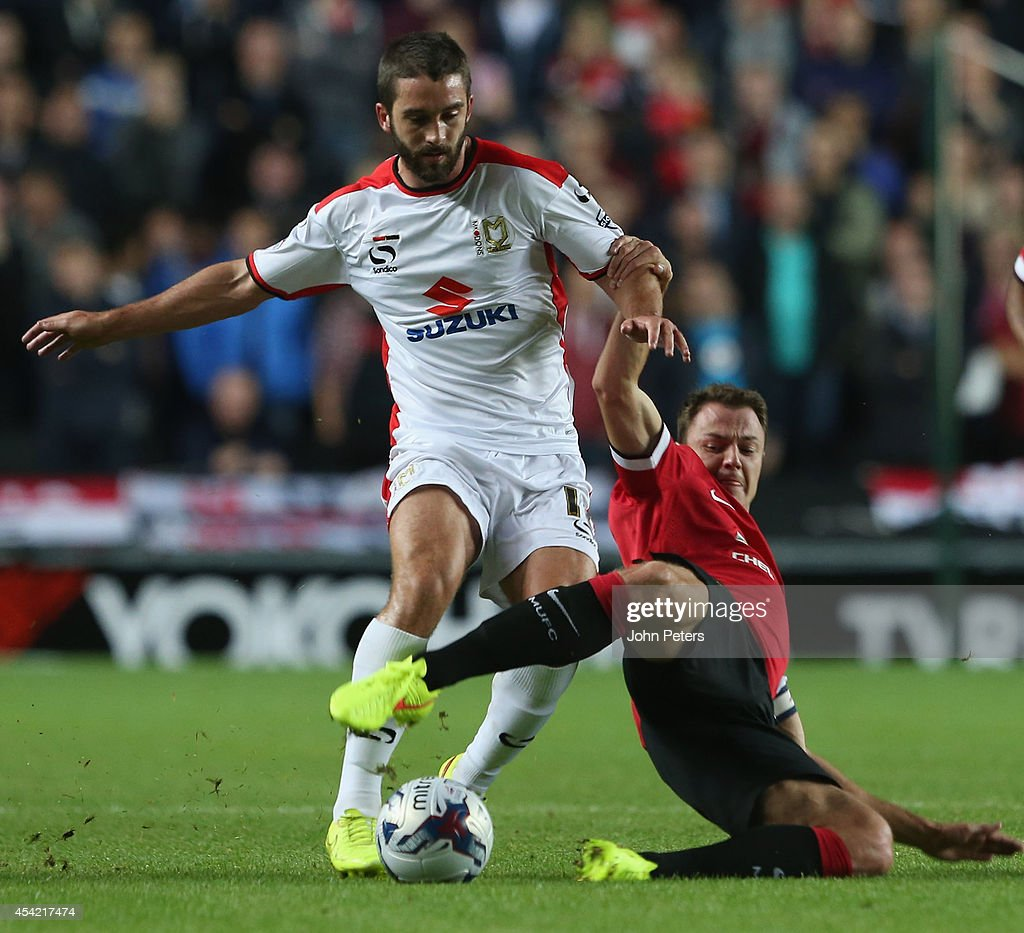 Jonny Evans of Manchester United in action with Will Grigg of MK Dons during the Capital One Cup Second Round match between MK Dons and Manchester United at Stadium mk on August 26, 2014 in Milton Keynes, England.