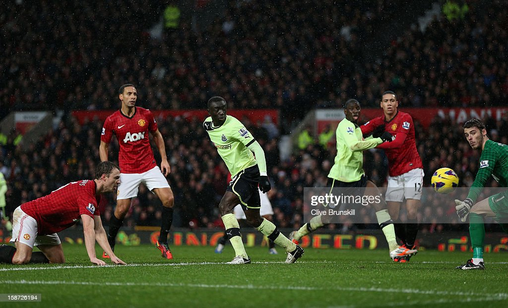 Jonny Evans of Manchester United watches as he scores an own goal past his keeper David De Gea watched by Papiss Cisse of Newcastle United during the Barclays Premier League match between Manchester United and Newcastle United at Old Trafford December 26, 2012 in Manchester, England.