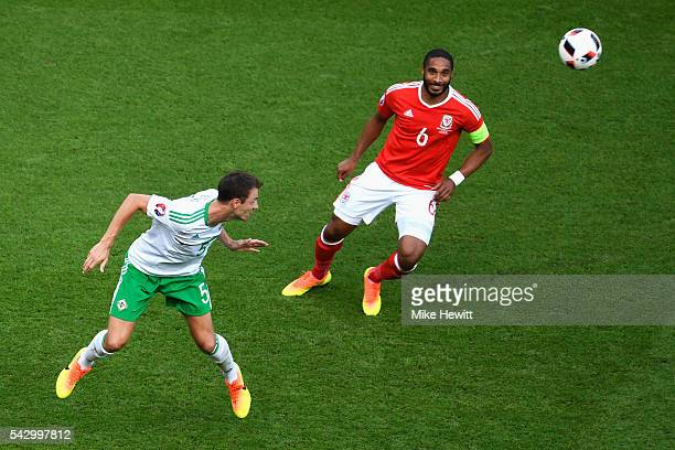 Jonny Evans of Northern Ireland heads the ball in front of Ashley Williams of Wales during the UEFA EURO 2016 round of 16 match between Wales and...