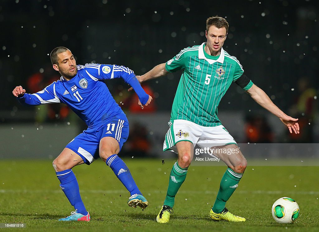 Jonny Evans of Northern Ireland holds off a challenge from Itay Shechter of Israel during the FIFA 2014 World Cup Group F Qualifier match between Northern Ireland and Israel at Windsor Park on March 26, 2013 in Belfast, Northern Ireland.