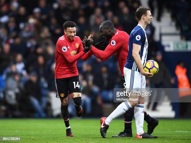 Jonny Evans of West Bromwich Albion looks dejected whilst Jesse Lingard of Manchester United celebrates with teammate Romelu Lukaku after scoring his...