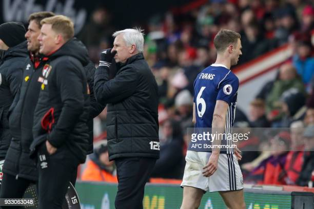 Jonny Evans of West Bromwich Albion passes West Brom manager Alan Pardew as he goes off injured during the Premier League match between AFC...