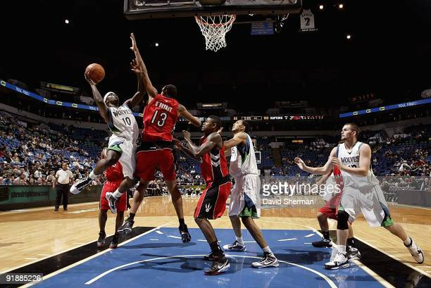 Jonny Flynn of the Minnesota Timberwolves goes to the basket under pressure against Patrick O'Bryant of the Toronto Raptors during the preseason game...