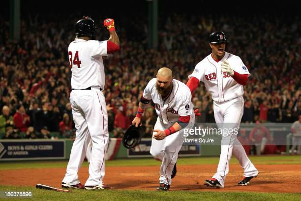 Jonny Gomes and David Ortiz of the Boston Red Sox celebrate after scoring in the third inning on a hit by Shane Victorino with Xander Bogaerts...