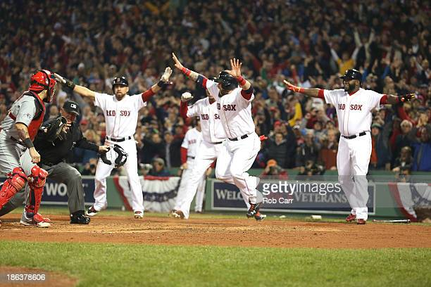 Jonny Gomes of the Boston Red Sox celebrates after sliding safely into home plate in the third inning against the St Louis Cardinals during Game Six...