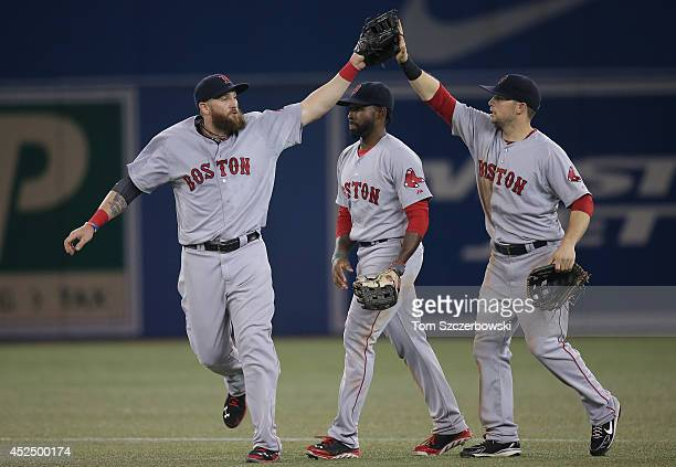 Jonny Gomes of the Boston Red Sox celebrates their victory with Jackie Bradley Jr #25 and Daniel Nava during MLB game action against the Toronto Blue...