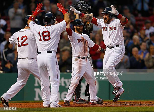 Jonny Gomes of the Boston Red Sox celebrates with Dustin Pedroia Mike Napoli and Shane Victorino after he hit a grand slam home run in the first...